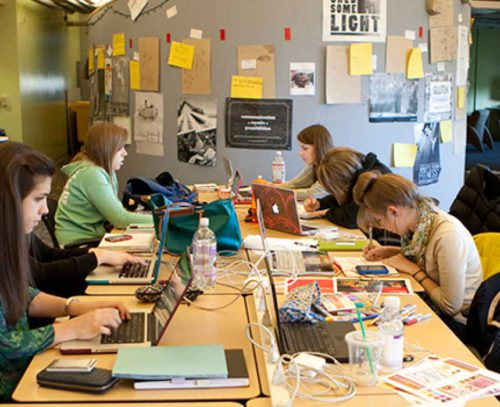 group of people sitting at a long table in front of laptops and materials working